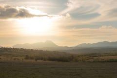 Złoty światło nad polami i górami Zdjęcie Royalty Free