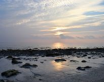 Złoty światło słoneczne z wzorem w bielu Chmurnieje w ranku niebie przy Skalistą plażą Naturalny tło - Kalapathar, Havelock, Anda fotografia stock