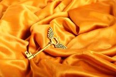 Złoty antyka klucz z skrzydłami na Złotym atłasowym tle zdjęcia royalty free