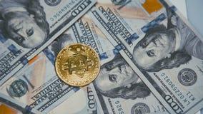 Złoty bitcoin krąży na rachunkach 100 dolarów 4K zbiory wideo