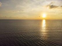 Złoty godzina zmierzch nad oceanem z puszystymi chmurami i spokój wodą zdjęcia stock