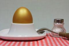 Złoty jajko w jajecznej filiżance na czerwonej wzorzystej pielusze Obrazy Royalty Free