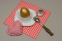 Złoty jajko w jajecznej filiżance na czerwonej wzorzystej pielusze Obraz Stock