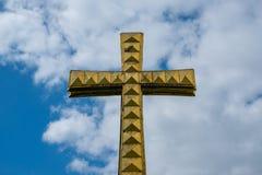 Złoty krzyż odizolowywający na nieba tle - chrześcijaństwo obraz stock