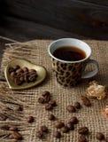 Złoty kształtujący spodeczek z piec kawowymi fasolami Zdjęcie Royalty Free