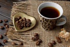 Złoty kształtujący spodeczek z piec kawowymi fasolami Zdjęcie Stock