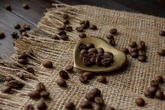 Złoty kształtujący spodeczek z piec kawowymi fasolami Obrazy Royalty Free