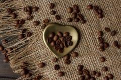 Złoty kształtujący spodeczek z piec kawowymi fasolami Zdjęcia Royalty Free