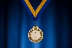 Złoty medal na zmroku - błękitny tło Zdjęcie Royalty Free