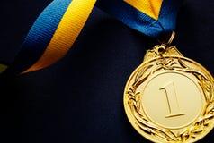 Złoty medal na zmroku - błękitny tło Obraz Stock