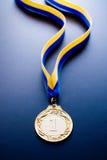 Złoty medal na zmroku - błękitny tło Obrazy Royalty Free