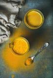 Złoty mleko z turmeric proszkiem w szkłach nad ciemnym tłem Zdjęcia Royalty Free
