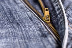 Złoty mosiężny suwaczek na niebieskich dżinsach Selekcyjna ostrość Fotografia Stock