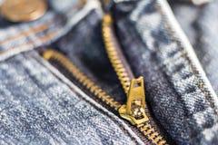 Złoty mosiężny suwaczek na niebieskich dżinsach Selekcyjna ostrość Zdjęcie Royalty Free