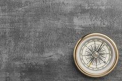 Złoty nawigacyjny kompas na rocznik szarość tle zdjęcie stock