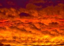Złoty Ognisty zmierzch z płatowatymi chmurami zdjęcie stock