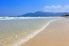 Złoty piaska i fala niebieskiego nieba światła dziennego plażowy krajobraz Fotografia Stock