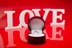 Złoty pierścionek w pudełku na czerwonym tle Fotografia Royalty Free