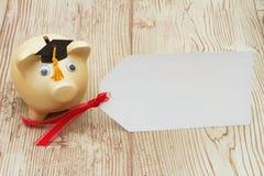 Złoty prosiątko bank z absolwenta prezenta i nakrętki etykietką na drewnianym backgroun Fotografia Stock