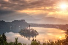 Złoty wschód słońca nad sławnym wysokogórskim jeziorem Krwawił z wniebowzięciem Mary pielgrzymki kościół na wyspie, Slovenia obraz stock