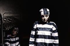 Zły żeński więzień jest ubranym więzienia jednolitego trwanie pobliskiego łóżko w Obraz Stock
