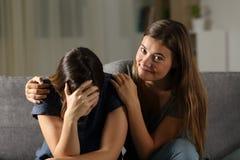 Zły nastoletni jest szczęśliwy z jej smutnym przyjaciela płaczem obraz royalty free