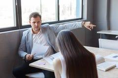 Zły szef w biurze wskazuje młodej dziewczyny ` s palec przy wyjściem Zdjęcia Stock