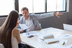 Zły szef w biurze wskazuje młodej dziewczyny ` s palec przy wyjściem Fotografia Stock