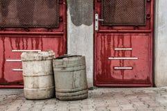 Z śmieciarskimi koszami starzy czerwoni drzwi fotografia royalty free