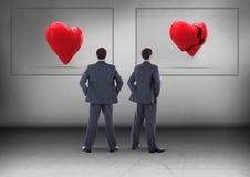 Złamane serce lub serce w ramach z biznesmenem patrzeje w opposite kierunkach Zdjęcia Stock