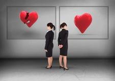 Złamane serce lub serce w ramach z bizneswomanem patrzeje w opposite kierunkach Zdjęcie Royalty Free