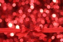 Z błyskotliwości tłem czerwony łęk. Obrazy Royalty Free