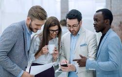 z bliska biznes drużyna dyskutuje podczas gdy stojący w biurze zdjęcia royalty free