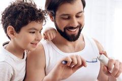 z bliska Brodaty ojciec pokazuje młodemu synowi dlaczego gnieść pastę do zębów na toothbrush zdjęcie stock