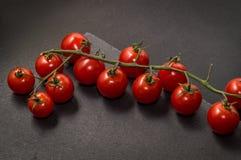 z bliska Jaskrawi czerwoni świezi czereśniowi pomidory na tnącej desce Czarny tło kosmos kopii zdjęcie royalty free