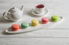 z bliska Provence ciasta śniadaniowi Kolorowi macarons rozkładający na ściągłym talerzu, filiżanka jagodowa herbata, teapot fotografia stock