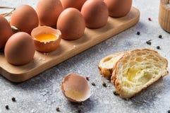 z bliska Tradycyjny tuzin A śniadania rolni jajka w drewnianej tacy obok kawałów baguette z serem i pieprzem, obrazy royalty free