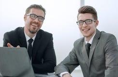 z bliska uśmiechnięci partnery biznesowi siedzi przy biurkiem zdjęcie royalty free