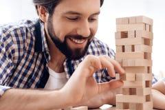 z bliska Uśmiechnięty brodaty mężczyzna usuwa drewnianych bloki od wierza zdjęcie stock