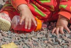 Z butelką w rękach dziecko na skałach Zdjęcia Stock