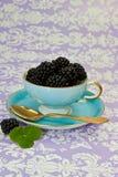 Z czarny jagodami herbaciana rocznik filiżanka Zdjęcia Stock