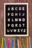 A-Z en bois d'alphabet anglais sur le tableau noir Crayon de couleur sur l'OE Photographie stock