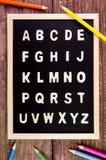 A-Z en bois d'alphabet anglais sur le tableau noir Crayon de couleur sur l'OE Photo stock