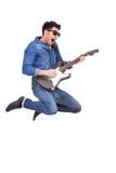 Z gitarą młodego człowieka doskakiwanie Fotografia Royalty Free