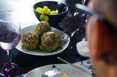 Z klasą obiadowego stołu położenie, gotujący karczochy siedzi w środku obok zielonych winogron, lewa strona obsługuje głowę i Zdjęcie Stock