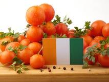 Z kości słoniowej wybrzeża flaga na drewnianym panelu z pomidorami odizolowywającymi na w obrazy stock
