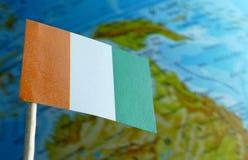 Z kości słoniowej wybrzeża flaga z kuli ziemskiej mapą jako tło zdjęcia stock