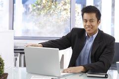 Z laptopem szczęśliwy biznesmen obrazy stock