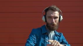 Z he?mofonami szcz??liwy m?ody cz?owiek Słuchać muzyka i taniec na czerwonym tle swobodny ruch zdjęcie wideo