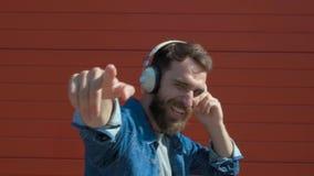 Z he?mofonami szcz??liwy m?ody cz?owiek Słuchać muzyka i taniec na czerwonym tle swobodny ruch zbiory wideo